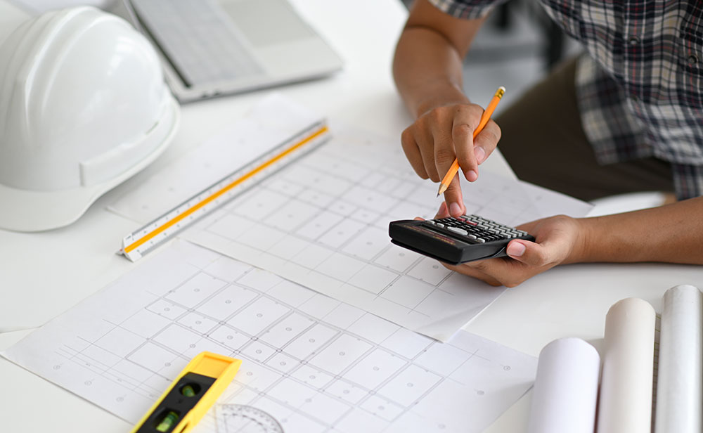 Architect uses calculator to estimate construction costs